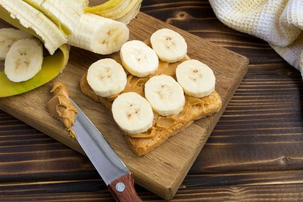 Tosty z pastą orzechową i bananem na desce do krojenia