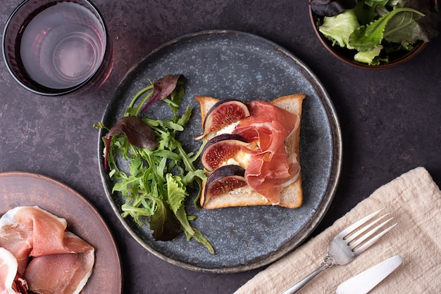Tosty z prosciutto i figami, crostini z włoską szynką i ricottą, przekąska na ciemnym tle, zbliżenie.