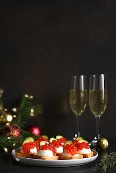 Tosty z serem i czerwonym kawiorem na stole noworocznym z szampanem. stół noworoczny. przekąska.