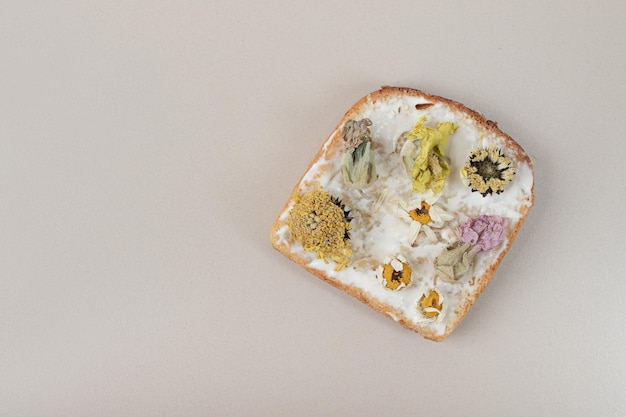 Tosty z suszonymi kwiatami i mąką na szarym stole.