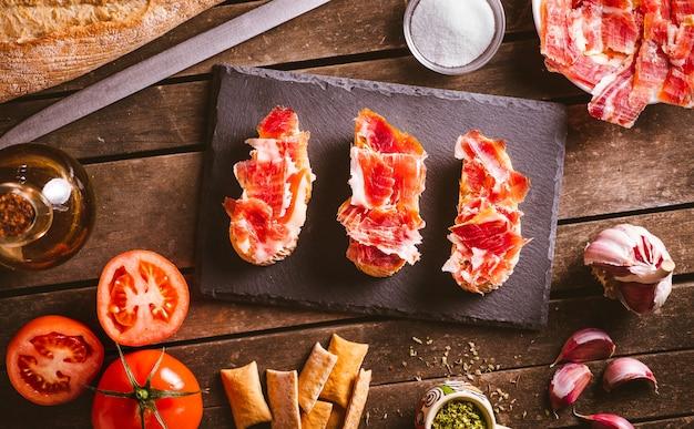 Tosty z szynki iberyjskiej na łupkowym talerzu na brązowym drewnianym stole z kilkoma składnikami wokół niego