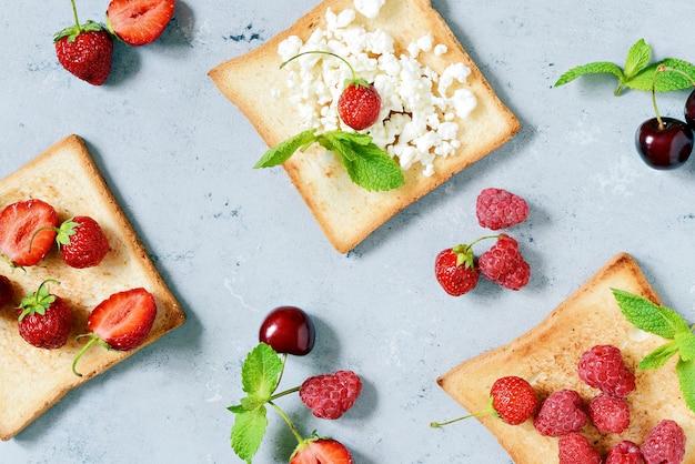 Tosty z truskawkami, malinami, wiśniami, miętą i twarogiem na śniadanie. zdrowe śniadanie, grzanka z rumianego chleba. tradycyjne amerykańskie i europejskie letnie śniadanie: kanapki z tostem
