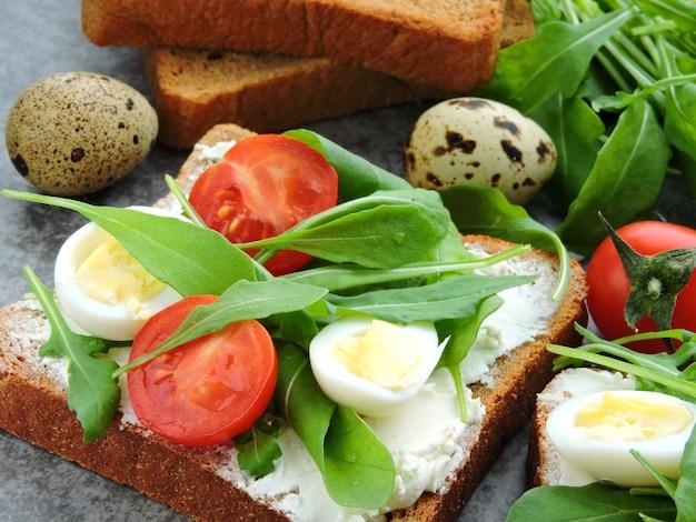 Tosty z żyta pszennego z rukolą, jajkami przepiórczymi i pomidorami cherry.