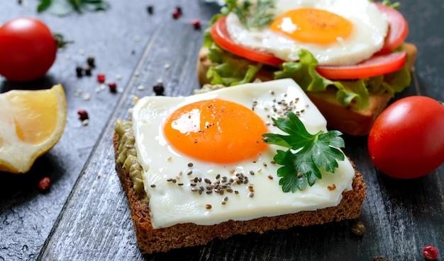 Tosty żytnie z puree z awokado, jajkiem sadzonym, świeżym pomidorem, ziołami. smaczne śniadanie. odpowiednie odżywianie. kanapka z jajkiem.