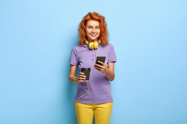 Towarzyska komunikatywna dziewczyna wysyła sms-y przez smartfon, pije kawę z papierowego kubka
