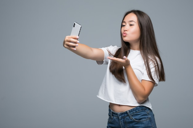 Towarzyska piękna azjatykcia dziewczyna bierze selfie lub mówi na rozmowie wideo używać telefon komórkowego nad szarym tłem