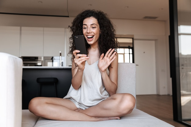 Towarzyska, urocza kobieta siedzi ze skrzyżowanymi nogami na kanapie w domu i macha ręką podczas rozmowy wideo z telefonu komórkowego