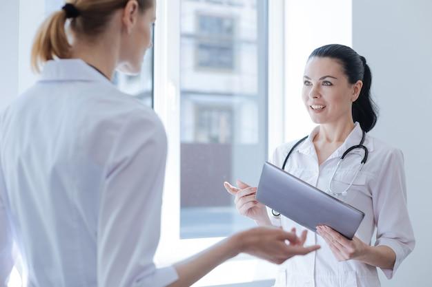 Towarzyski, pozytywny młody lekarz pracujący w szpitalu i prowadzący rozmowę, trzymając urządzenie cyfrowe