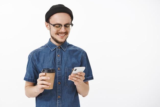 Towarzyski szczęśliwy i zrelaksowany młody stylowy nowoczesny i nieogolony facet w okularach czarna czapka i niebieska koszula trzymający smartfona i papierowy kubek z kawą uśmiechający się radośnie do ekranu urządzenia
