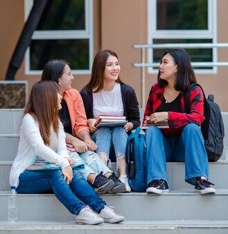 Towarzystwo azjatyckich studentek zbierających się na schodach w kampusie uniwersyteckim i wspólnie omawiających projekt z laptopem i podręcznikami. intymny towarzysz w koncepcji uczelni.