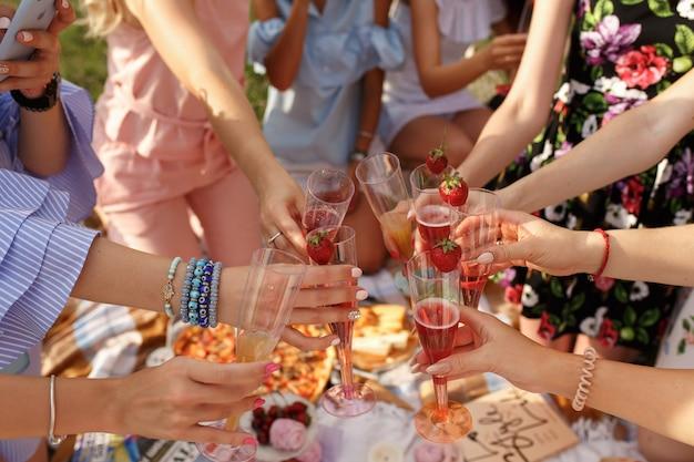 Towarzystwo dziewczyn wiwatuje na pikniku.