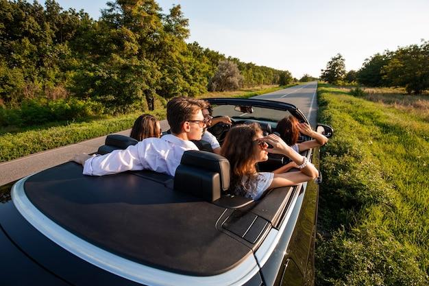 Towarzystwo młodych dziewcząt i chłopaków siedzi w czarnym kabriolecie na wiejskiej drodze w słoneczny dzień. .