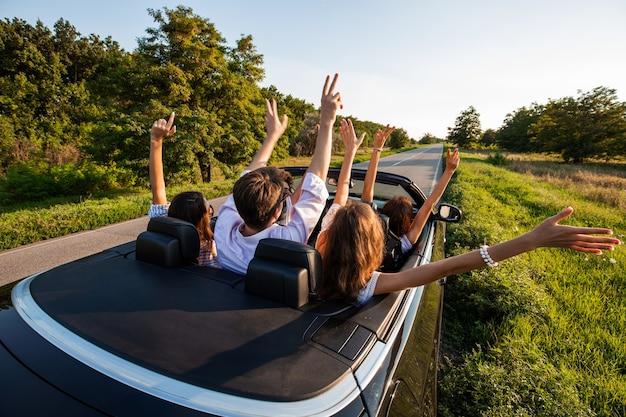 Towarzystwo młodych dziewcząt i chłopaków siedzi w czarnym kabriolecie, trzymając ręce do góry na wiejskiej drodze w słoneczny dzień. .