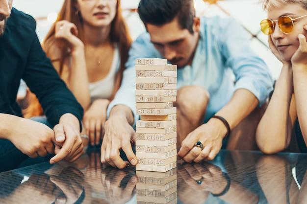 Towarzystwo młodych ludzi grających w gry planszowe