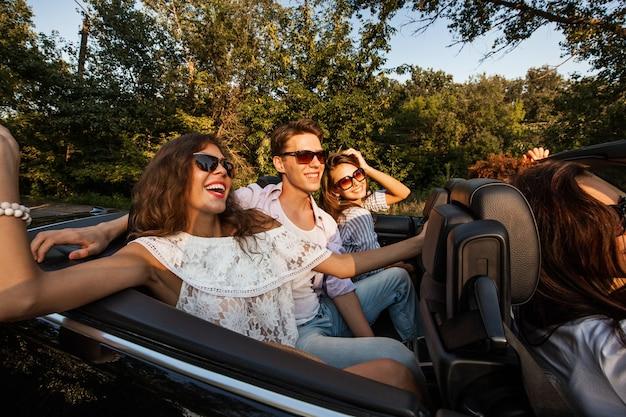 Towarzystwo młodych ludzi jadących kabrioletem na drodze w ciepły słoneczny dzień. dwie piękne dziewczyny i młody mężczyzna między nimi siadają na tylnym siedzeniu i uśmiechają się. .