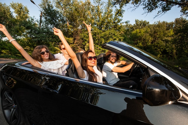 Towarzystwo młodych ludzi jadących kabrioletem na drodze w ciepły słoneczny dzień... dwie piękne dziewczyny trzymające się za ręce. .