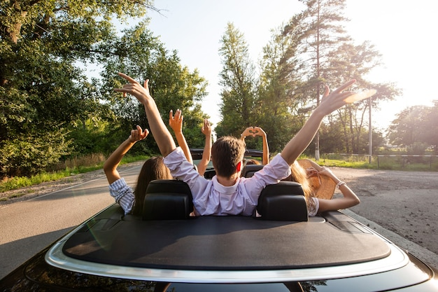 Towarzystwo młodych ludzi jeżdżących kabrioletem na drodze i trzymających ręce w górę w ciepły słoneczny dzień. widok z tyłu. .