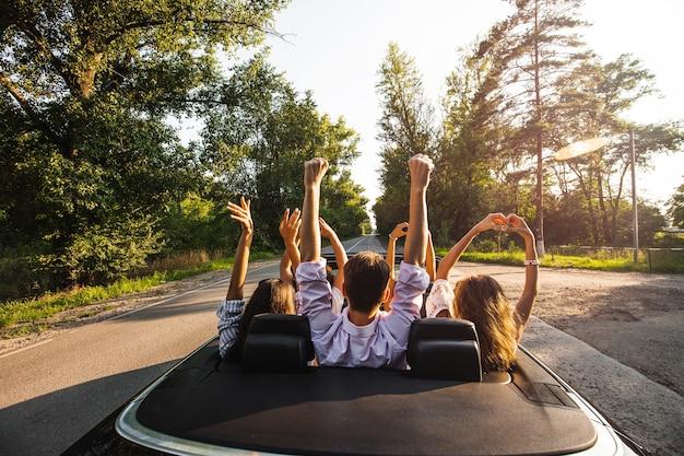 Towarzystwo młodych ludzi jeżdżących kabrioletem na drodze i trzymających ręce w górę w ciepły słoneczny dzień. .