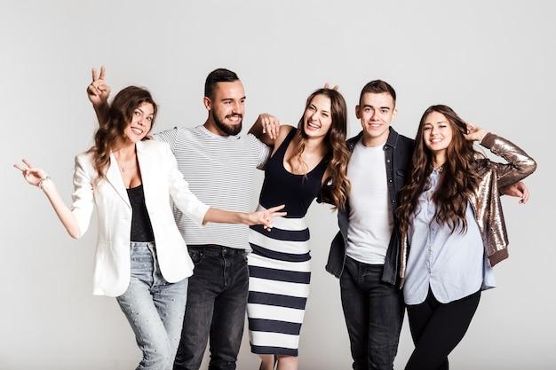 Towarzystwo młodych ludzi ubranych w stylowe, casualowe ciuchy uśmiecha się i bawi się razem na białym tle w studio.
