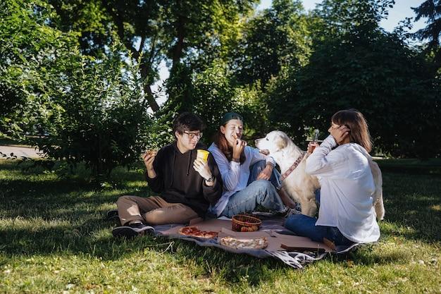Towarzystwo pięknych młodych ludzi jedzących lunch na świeżym powietrzu. koncepcja jedzenia fast food.