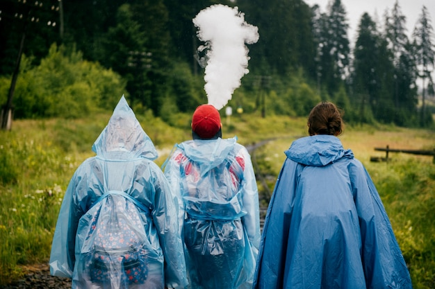 Towarzystwo przyjaciół idących wzdłuż torów kolejowych. dwie dziewczyny z chłopcem w niebieskich płaszczach chodzą na linii kolejowej na świeżym powietrzu w przyrodzie w pochmurny deszczowy dzień. portret z tyłu trzech towarzyszy podróżujących razem
