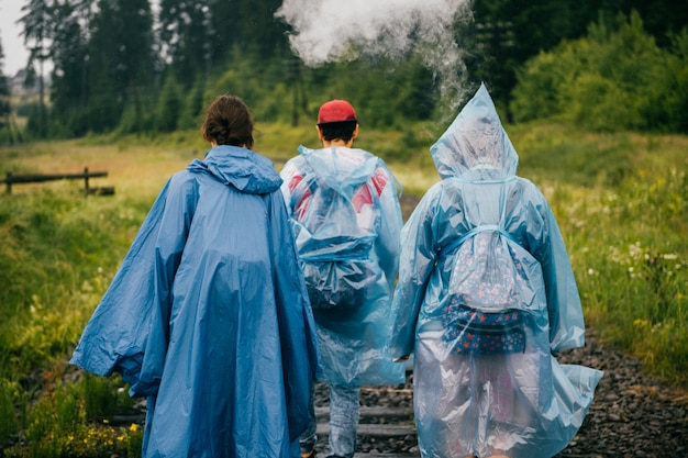 Towarzystwo przyjaciół idących wzdłuż torów kolejowych.