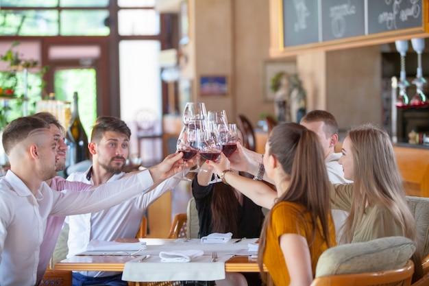Towarzystwo przyjaciół świętuje spotkanie w restauracji.