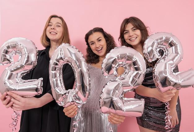 Towarzystwo szczęśliwych dziewczyn na różowym tle ze srebrnymi balonami foliowymi w postaci cyfr 2022, świętujących nowy rok.
