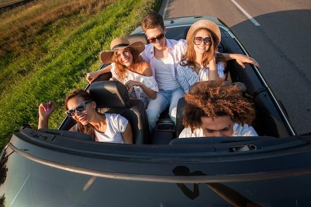 Towarzystwo szczęśliwych młodych dziewcząt i chłopaków siedzą na drodze czarnego kabrioletu w słoneczny dzień. widok z góry .