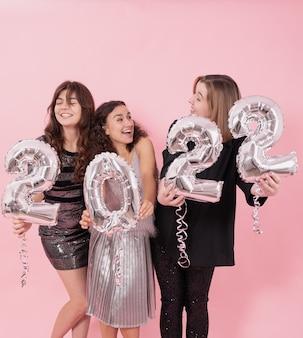 Towarzystwo wesołych dziewczyn na różowym tle ze srebrnymi balonikami w postaci cyfr 2022.