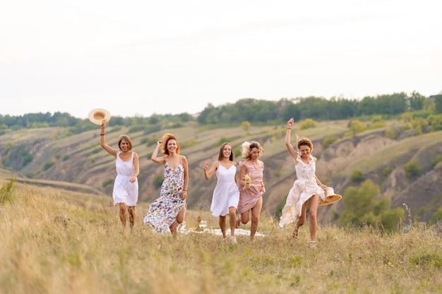 Towarzystwo wesołych koleżanek spędza miło czas na pikniku w malowniczym miejscu z widokiem na zielone wzgórza. dziewczyny w białych sukienkach tańczą w terenie