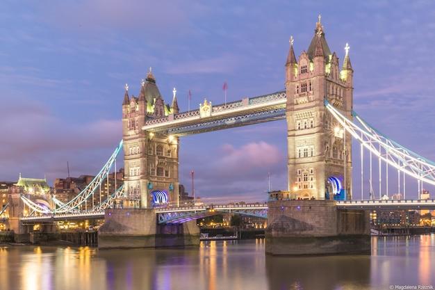 Tower bridge otoczony budynkami i światłami wieczorem w londynie w wielkiej brytanii