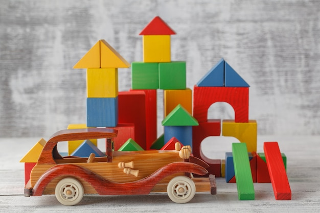 Toy blocks city, baby house building bricks, kids wooden cubic over white wall