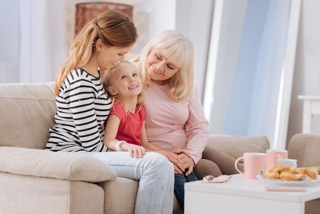 Tradycje rodzinne. śliczna radosna szczęśliwa dziewczyna uśmiechając się i patrząc na matkę, spędzając czas z rodziną