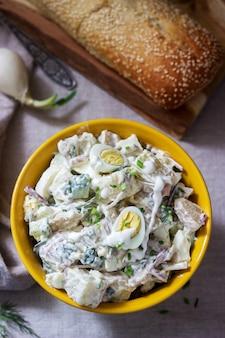 Tradycyjna amerykańska sałatka ziemniaczana z jajkiem i majonezem, podawana z chlebem. styl rustykalny.
