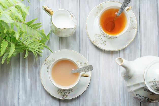 Tradycyjna angielska herbata o godzinie 17:00 w eleganckim zestawie z porcelany. dwie filiżanki herbaty i mleka na drewnianej tacy vintage. leżał na płasko.