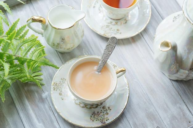Tradycyjna angielska herbata o godzinie 17:00 w eleganckim zestawie z porcelany. dwie filiżanki herbaty i mleka na drewnianej tacy vintage. widok z góry.