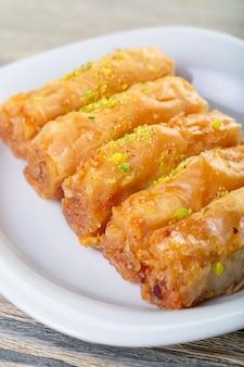 Tradycyjna arabska baklava deserowa z orzechami nerkowca, orzechami włoskimi i kardamonem z gałęzią eukaliptusa na drewnianym stole