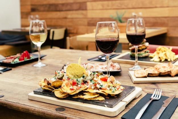 Tradycyjna atmosfera z kolorowym talerzem nachos doprawionych warzywami i kieliszkiem czerwonego wina na rustykalnym drewnianym stole
