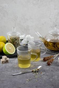 Tradycyjna azjatycka zielona herbata w szklanym imbryku. gorący zdrowy napój na ciemnym tle.