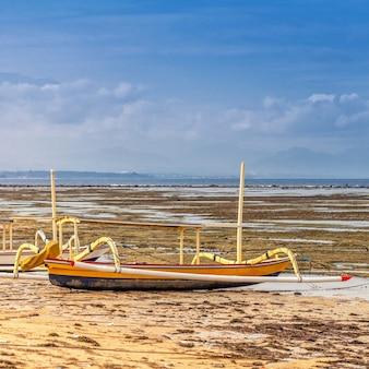 Tradycyjna balijska łódź rybacka stoi na brzegu oceanu podczas odpływu.