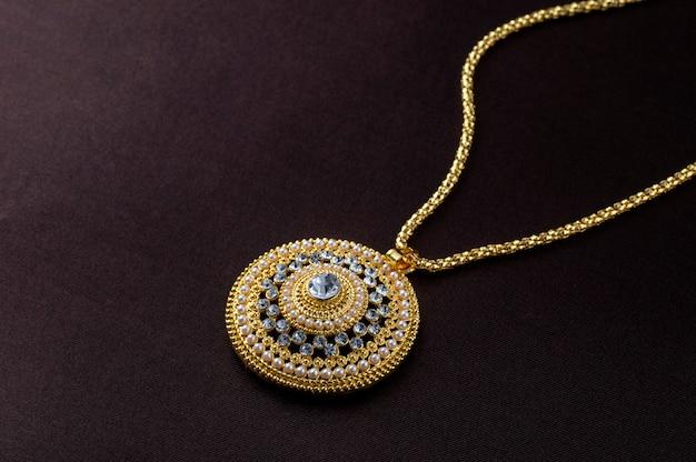 Tradycyjna biżuteria indyjska, bliska zawieszki na ciemnym tle