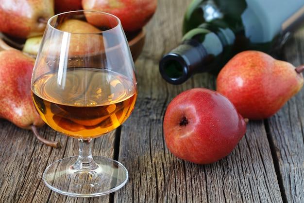Tradycyjna brandy owocowe i gruszki na drewniane tło