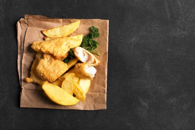Tradycyjna brytyjska ryba z frytkami na ciemnej powierzchni
