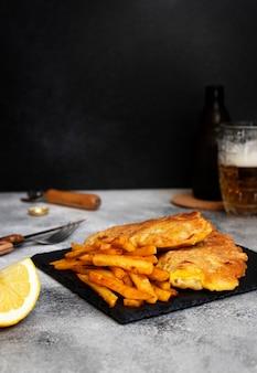 Tradycyjna brytyjska ryba z frytkami. na czarnym talerzu i szarym stole. podawany z cytryną i kubkiem zimnego piwa. czarne tło. miejsce na tekst