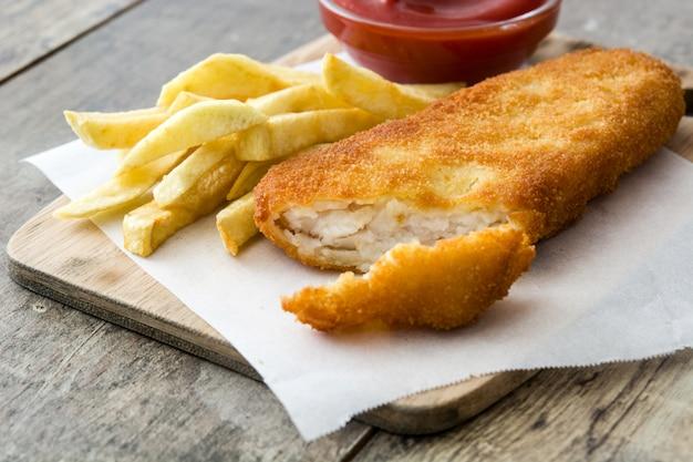 Tradycyjna brytyjska ryba z frytkami na drewnianym stole.