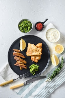 Tradycyjna brytyjska ryba z frytkami z dodatkiem miętowego puree z groszku i plasterkiem cytryny. na czarnej okrągłej płycie nad białymi lintn i kamiennym widokiem z góry.