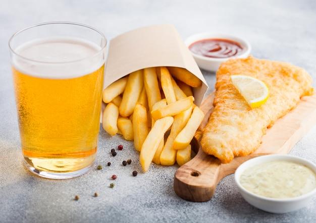 Tradycyjna brytyjska ryba z frytkami z sosem tatarskim i szklanką piwa typu lager oraz keczupem pomidorowym na desce do krojenia