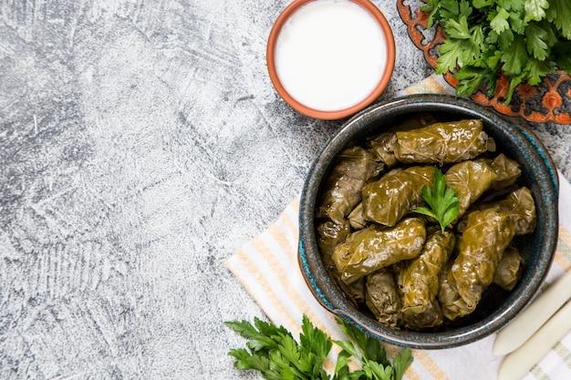 Tradycyjna dolma (sarma) w liściach winogron z copyspace. liban turecka grecka kuchnia bliskowschodnia. dolmadakia obiadowa
