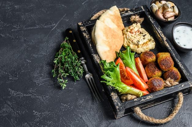 Tradycyjna domowej roboty ciecierzyca hummus, falafel, chleb pita i świeże warzywa.